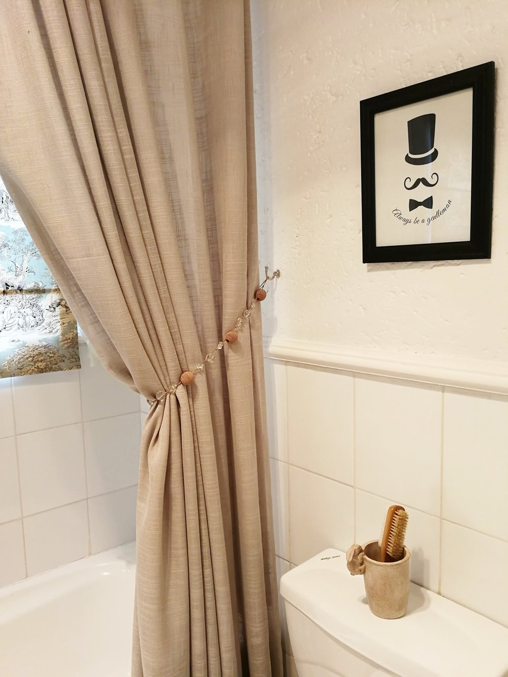 fabric shower curtain and wall art in neutral and black for a guest and baby bathroom