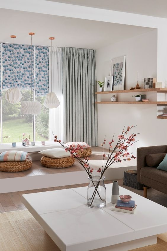 sheer curtains enveloped by light teal window treatments and patterned blinds.