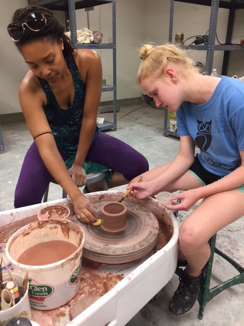 Tia Santana working with a summer student on refining her work on the wheel.