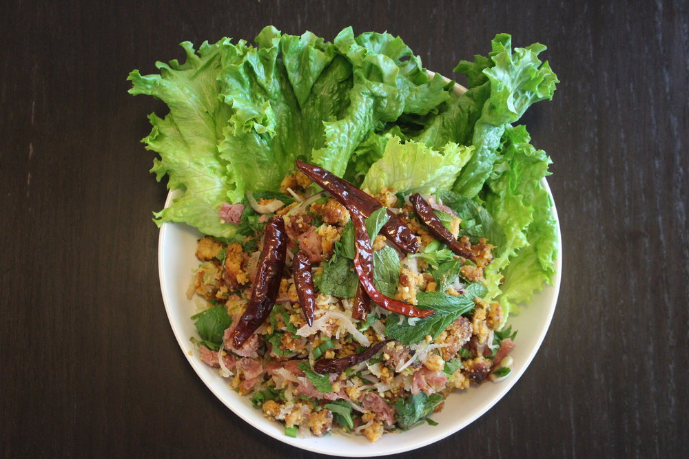 Dish Name: Nam Khao with Som Moo - Crispy Curry Rice & Cured Ham Dining Style: Nam Khao is traditionally served at room temperature and enjoyed by hand. Take some lettuce and stuff it with a spoonful of Nam Khao to create a lettuce wrap.