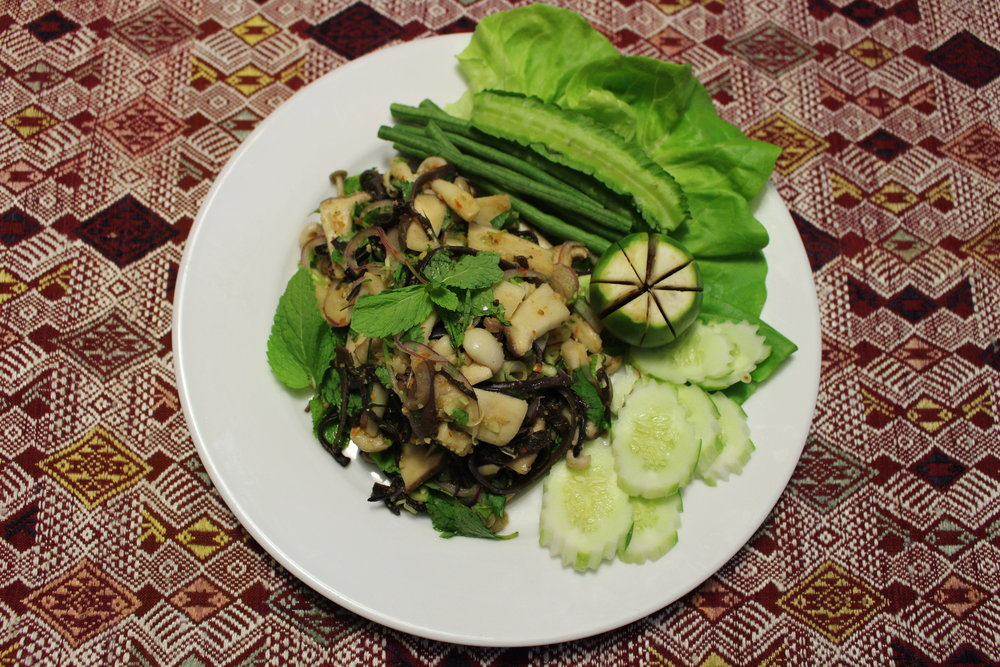 Dish Name: Larb Het - Spicy Mushroom Salad served with Khao Niaw - Sticky Rice Dining Style: Larb Het is traditionally served at room temperature and enjoyed by hand. You can then take some sticky rice and dip it into the Larb Het, creating a balanced bite of the Larb Het and sticky rice.