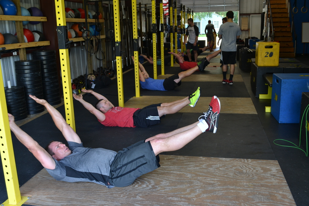 CrossFit competitors working on the hollow position to develop core strength & stability.