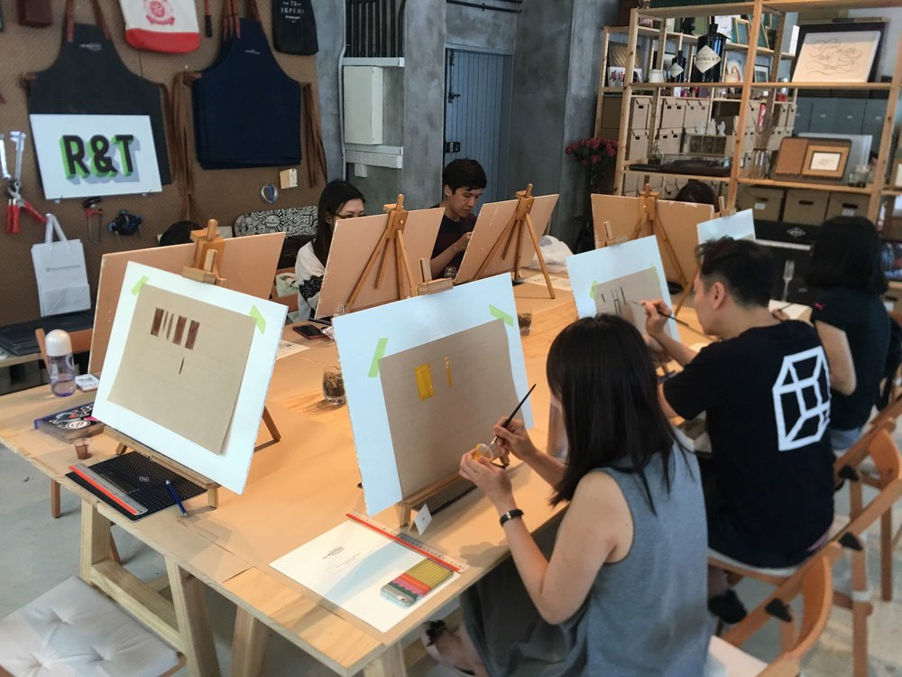 Participants preparing and trying to paint some simple shapes just to get the feel of painting with signpainting brushes.