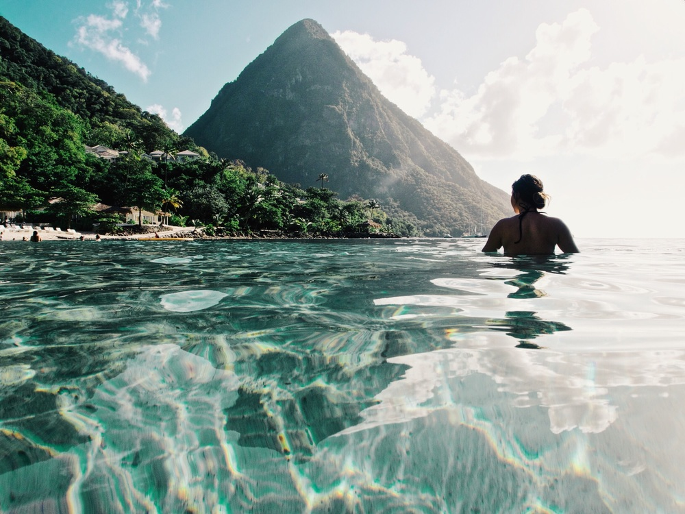 In the town of Soufrière, down a one way mountain road, long after the ruins, past the ⭐️5 star⭐️ villas, a whiff of suntan lotion and expensive shades, between the Piton mountains, is Sugar Beach. And it's hard to beat.