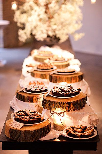 Dessert table with wood cake stands and glowing candles