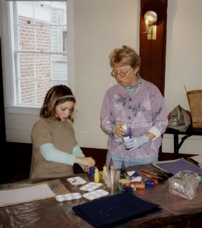 Jay and a young student painting on silk
