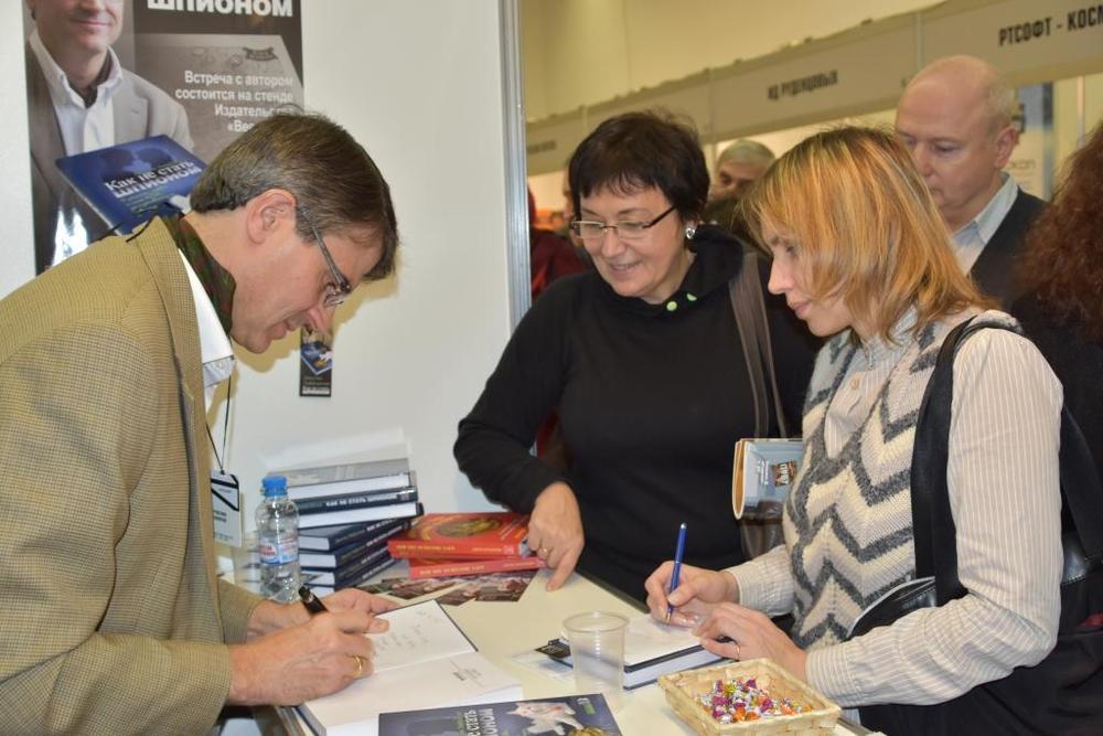 Подписываю книги для читателей и посетителей ярмарки