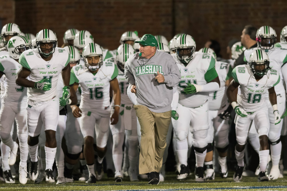 Marshall Thundering Herd head coach Doc Holliday leads the team onto the field prior to Saturday night's game against the Old Dominion Monarchs at Foreman Field in Norfolk, Virginia.