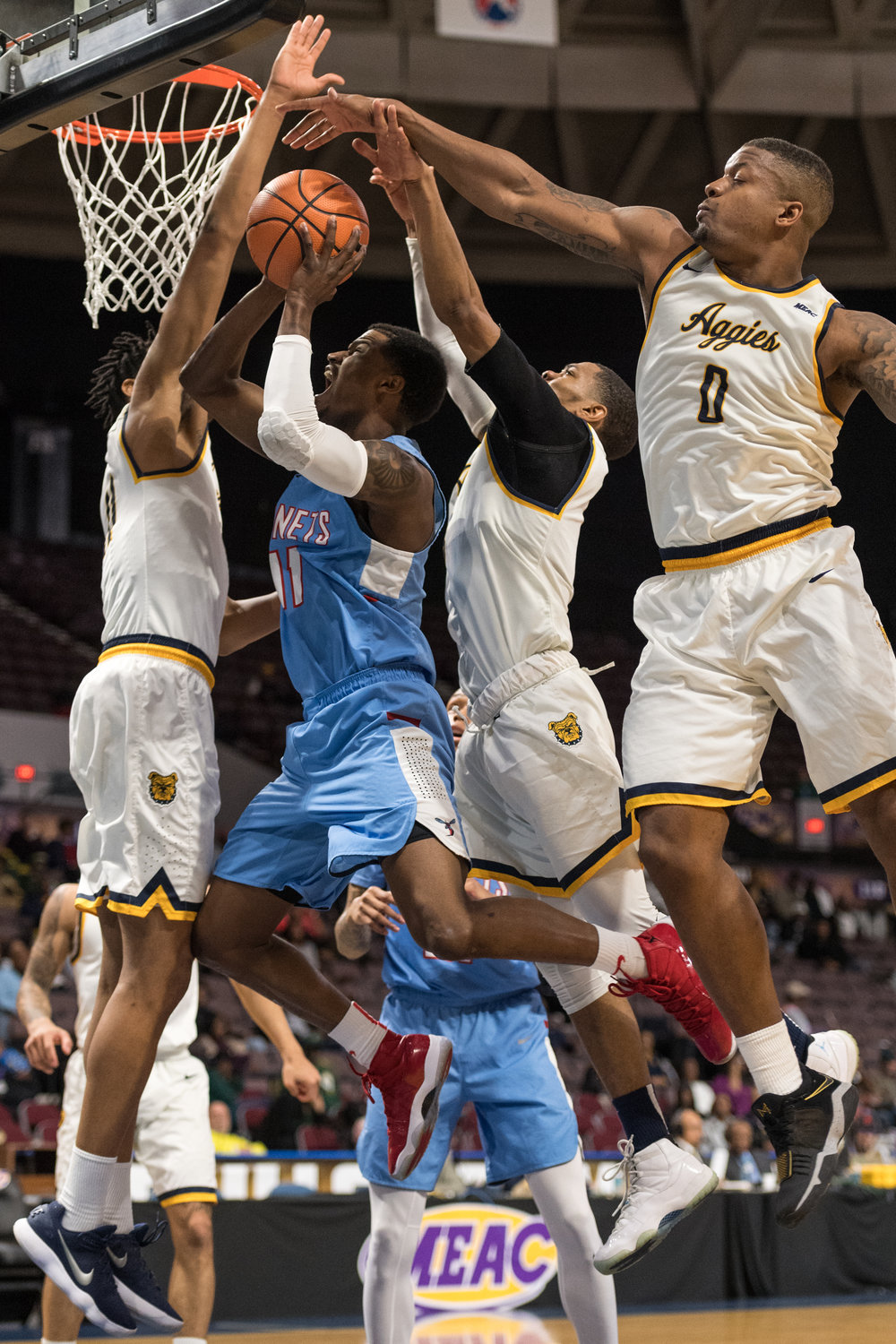 Delaware State Hornets guard Jonathan Walker (11) takes a shot under pressure from North Carolina A&T Aggies center D'Andre Johnson (11) guard Devonte Boykins (3) and forward Davaris McGowens (0) during the Monday, March 5, 2018 game held at Norfolk Scope Arena. North Carolina A&T defeated Delaware State 62 to 61 in overtime.