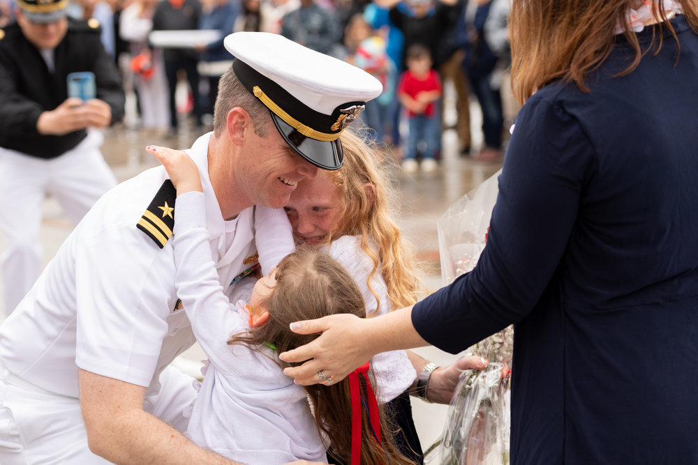 Lieutenant William Kuhn is greeted by his wife and children after the USS Monterey returned to Naval Station Norfolk on Sunday, May 6, 2018. The USS Monterey is returning from a seven month deployment to the Navy's 5th and 6th Fleets, culminating in missile strikes against Syria in April.