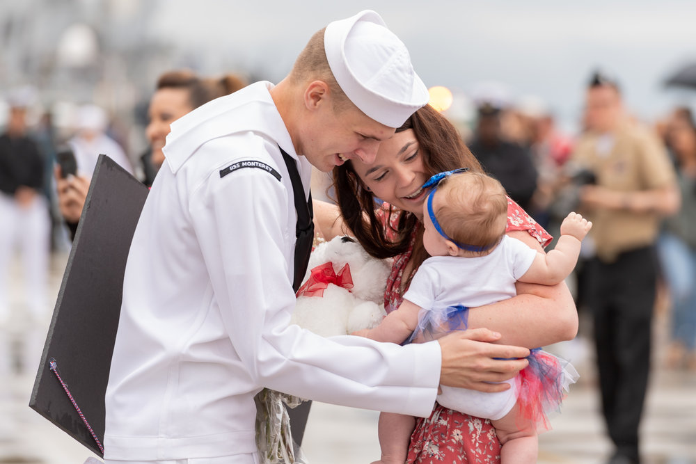 Fire Controlman 3rd Class Franke meets his child for the first time after the USS Monterey returned to Naval Station Norfolk on Sunday, May 6, 2018. The USS Monterey is returning from a seven month deployment to the Navy's 5th and 6th Fleets, culminating in missile strikes against Syria in April.