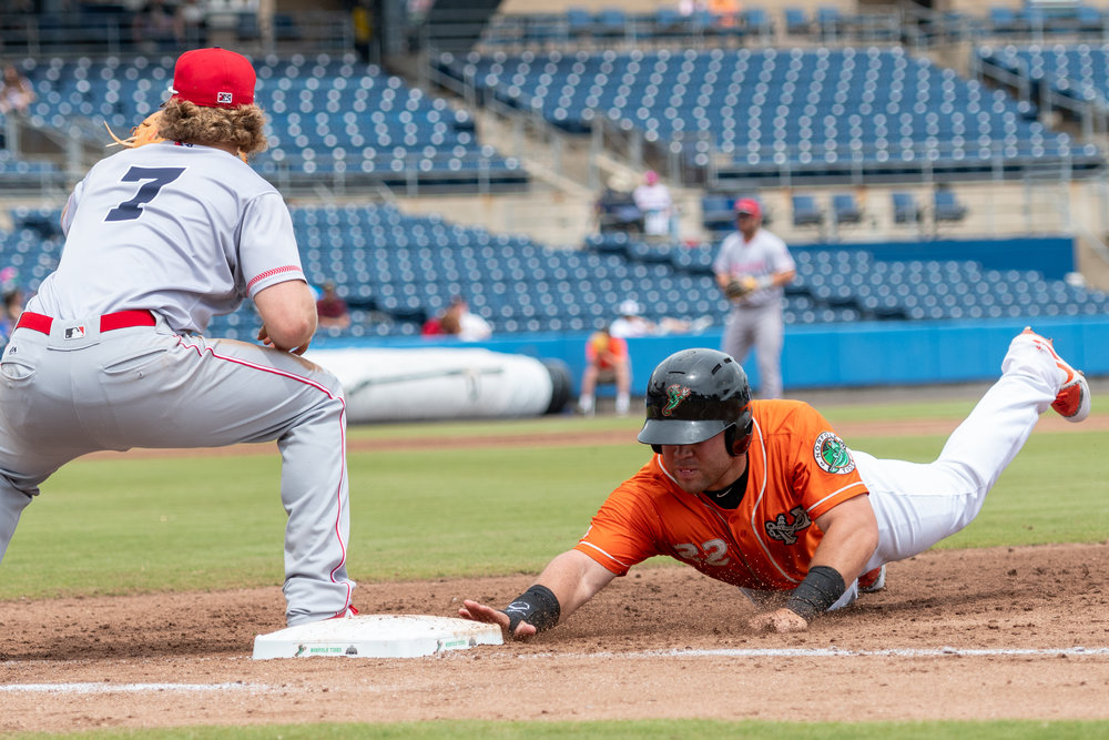 Norfolk Tides right fielder DJ Stewart dives safely back into first base against Louisville Bats first baseman Brandon Dixon during the Sunday, May 6, 2018 game at Harbor Park. The Tides defeated the Bats 2 - 1.