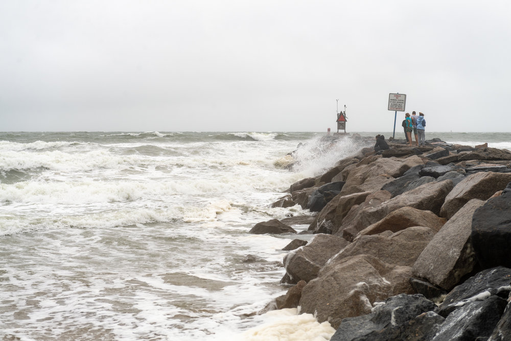 A group watch waves crash against the First Street Jetty as Hurricane Florence approaches the coast  on Thursday, September 13, 2018.