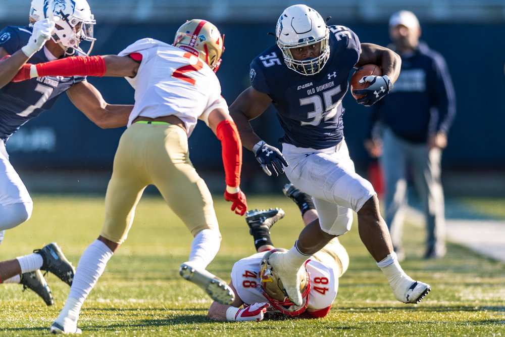 Old Dominion Monarchs running back Jeremy Cox (35) works to avoid a tackle by Virginia Military Institute Keydets defensive back Collin Loftis (2) and linebacker Brett Howell (48) during the Saturday, Nov. 17, 2018 game held at Old Dominion University in Norfolk, Virginia. Old Dominion leads VMI 49 to 0 at halftime.