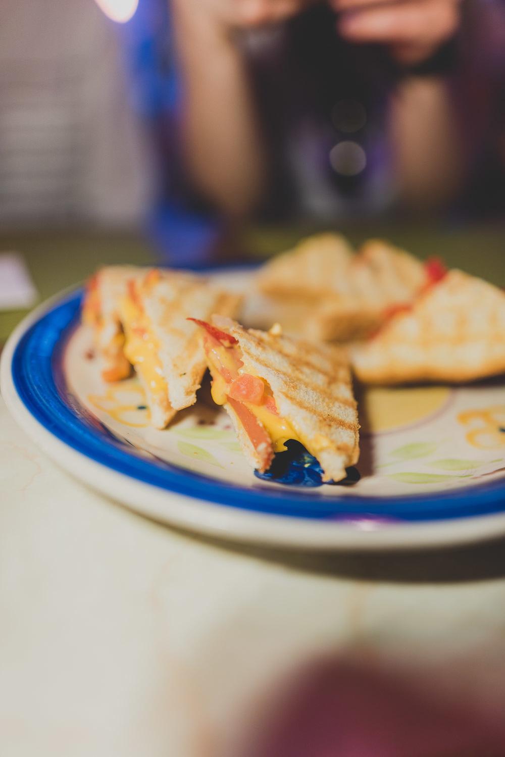 De la saucisse à hot-dog, des tomates, des oignons et quelques piments forts pour relever le tout, tendrement grillé entre tranches de pain et fromage jaune chez pour le Carrefour international de théâtre de Québec