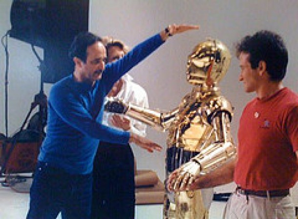 """Robin Williams & C-3PO (Anthony Daniels) take direction while shooting the """"Hands Across America"""" TV spot."""