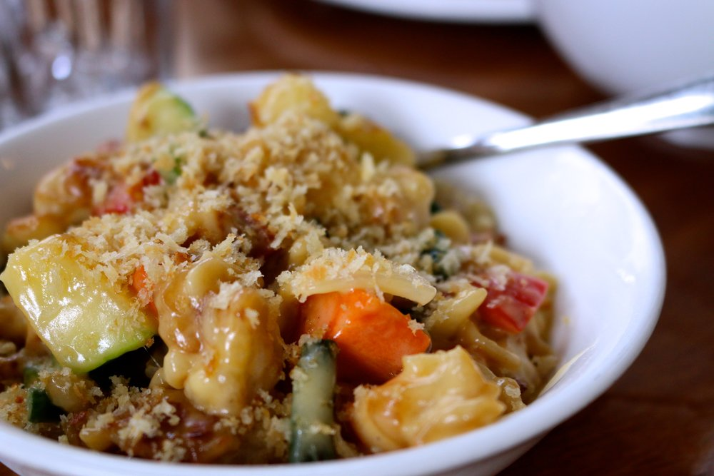 SPATZLE MAC N CHEESE - HOUSEMADE EGG NOODLES, MARKET VEG, WHITE WINE, AND CHEDDAR JACK.