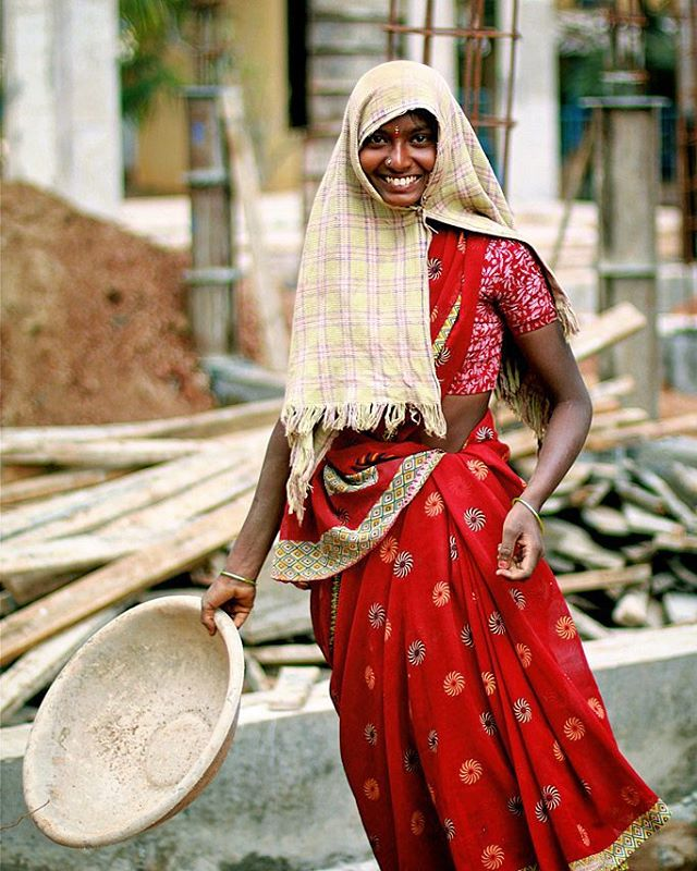 #India | #Asia  Portrait of a young woman at a building work.