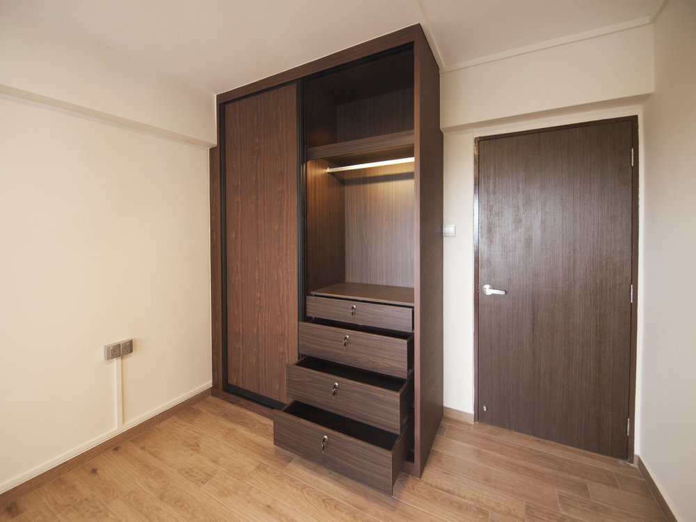 A sliding wardrobe with a concealed pull-out mirror under the ceiling beam.