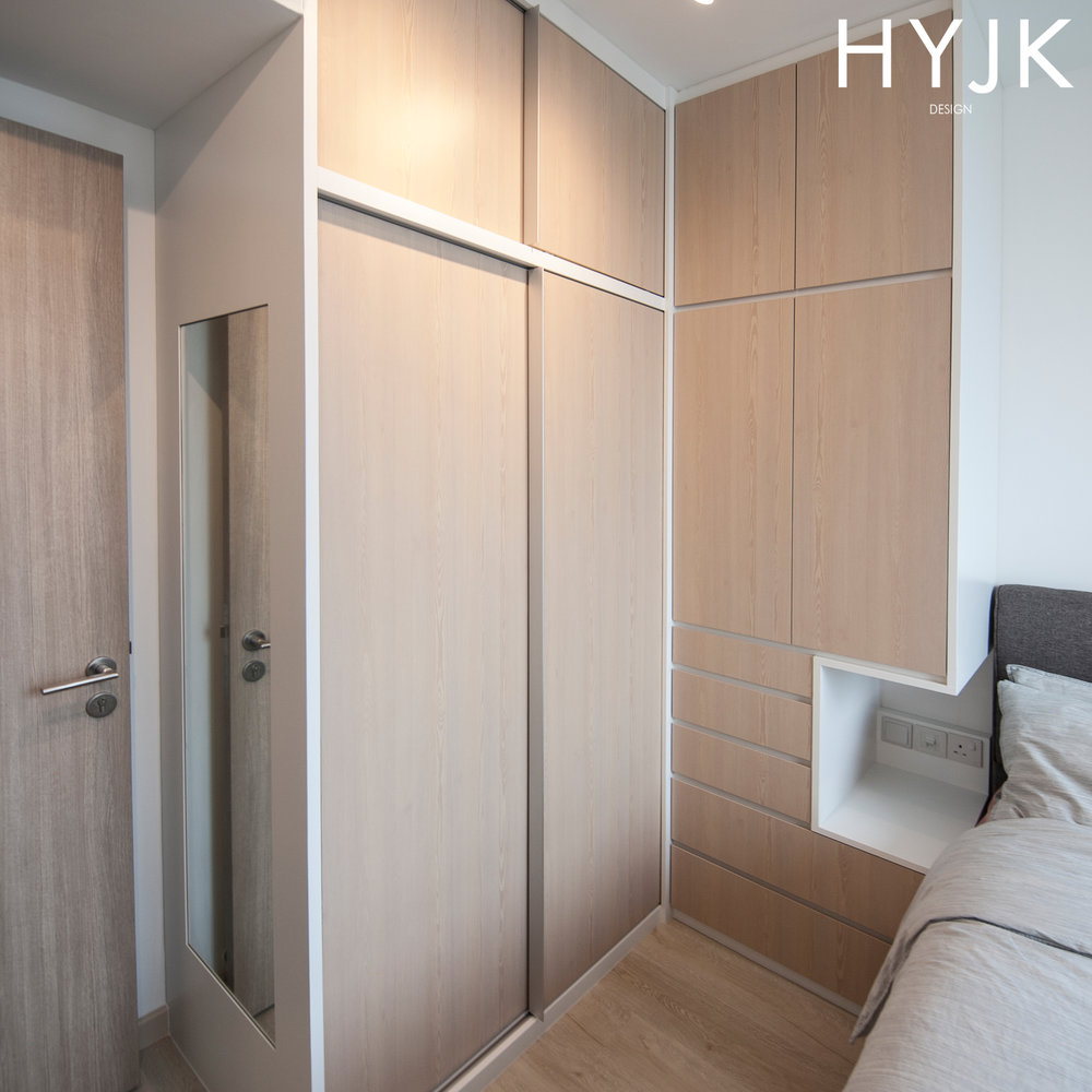 The L-shaped wardrobe maximizes storage and doubles up as a bedside table.