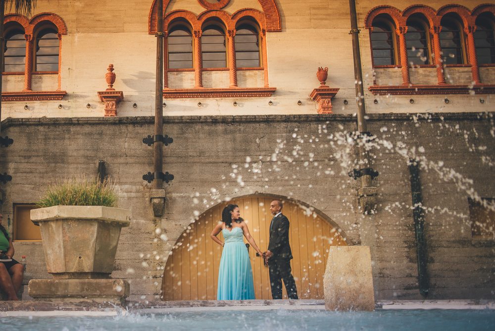 St. Augustine wedding and engagement photographer, Zack Glenn, of Bow Tie Photo takes a photograph of engaged couple Yamicia and Yoni behind the Lightner Museum by the water fountain during their engagement session.