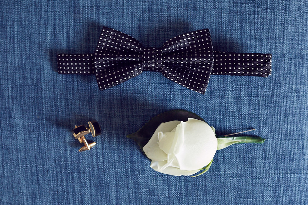 Simple white rosebud boutonniere paired with a dotted bow tie.