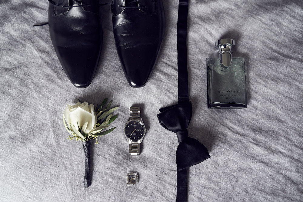 Black face Tag timepiece, Aquila shoes, BVLGARI cologe, Black bow tie & tiffany cufflinks paired with a white rosebud boutonniere.