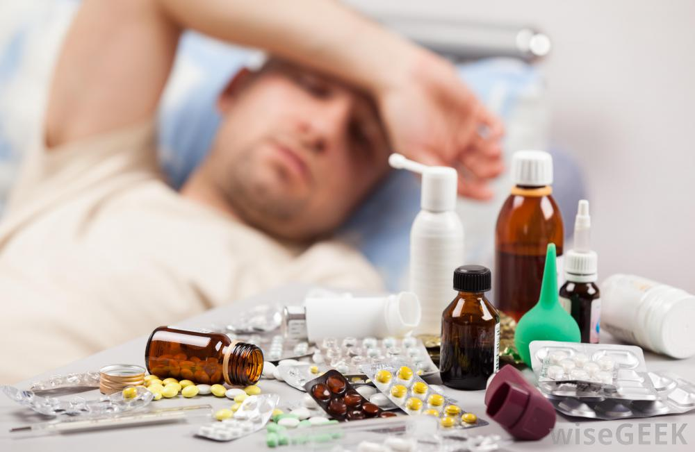 man-with-hand-over-his-head-feeling-ill-in-background-with-close-view-of-pills-and-medicine.jpg