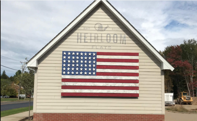 Tao created a mixed-media faded American flag and painted logo mural on an exterior wall near the entry to the  Heirloom Flats  apartment complex project. The artwork is reminiscent of folk art tradition of painting flags on the sides of barns.