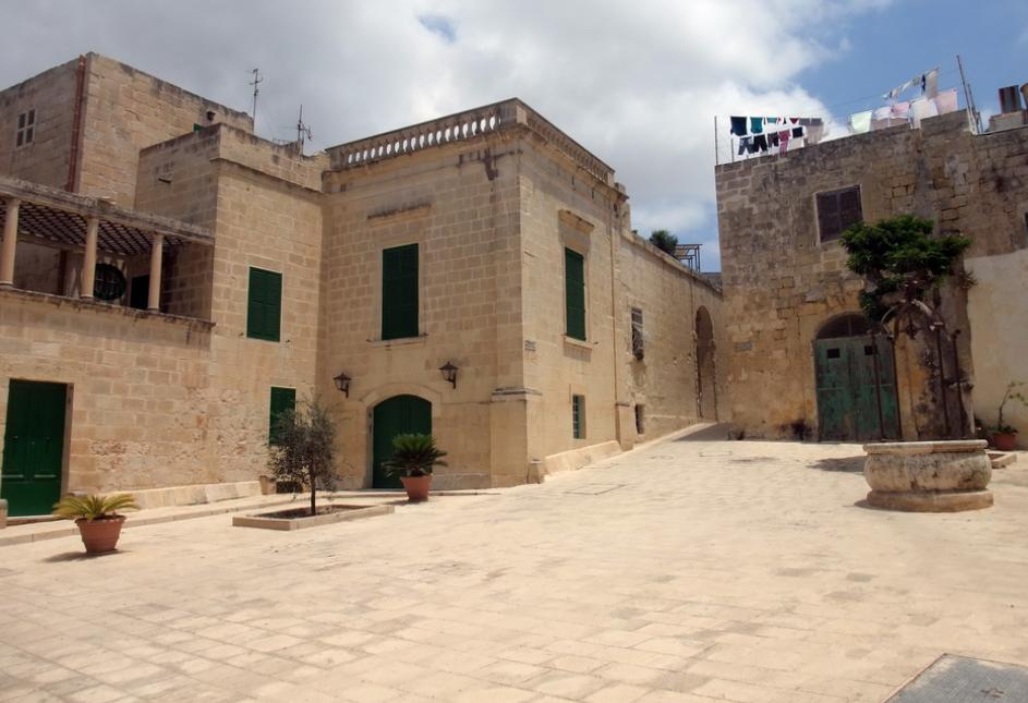 The empty Mesquita Square and,the trellised balcony of Petyr Baelish's bordello on the left.