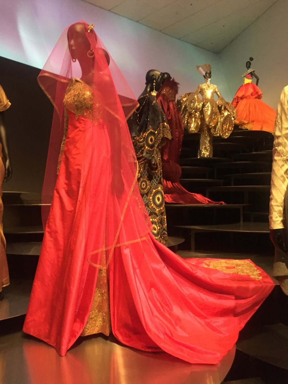 Ellora , a coral taffeta dress embroidered with gold lace by artistic designer Gianfranco Ferré, is featured among global-inspired couture dresses standing on massive steps of shaped like petals in the Martin and McCormick Gallery.
