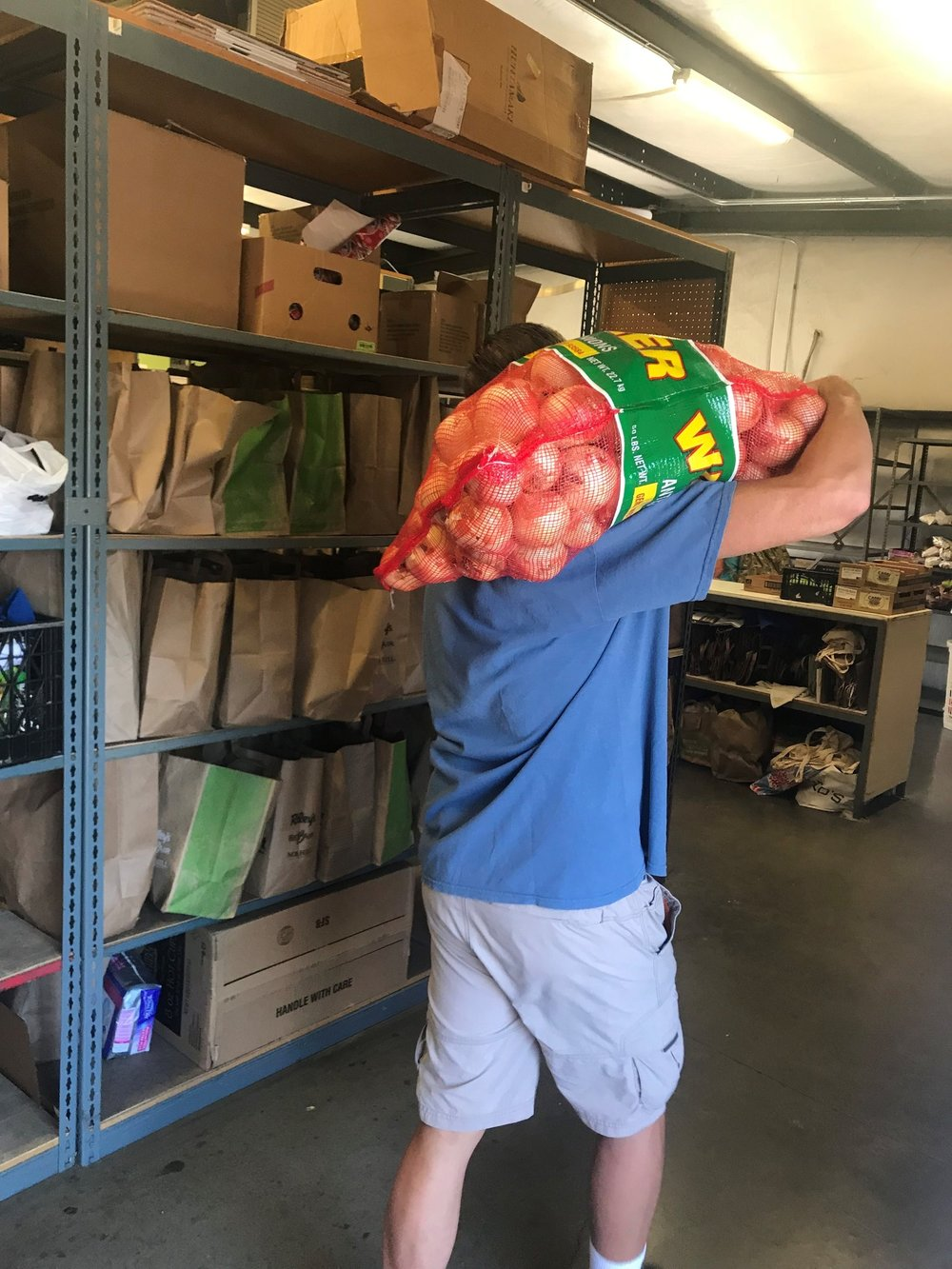 A volunteer offloads produce items he picked up at SFBFS.