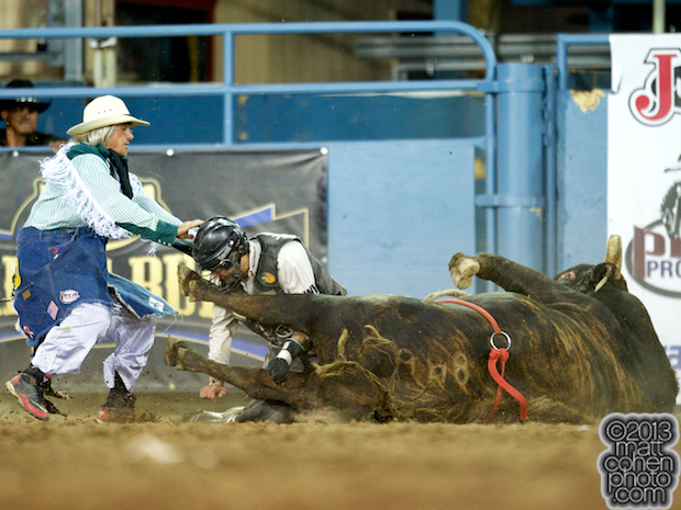 Bullfighter Donny Castle steps in to protect bull rider Ty Pozzobon of Merritt, B.C. who gets kicked by Snugly