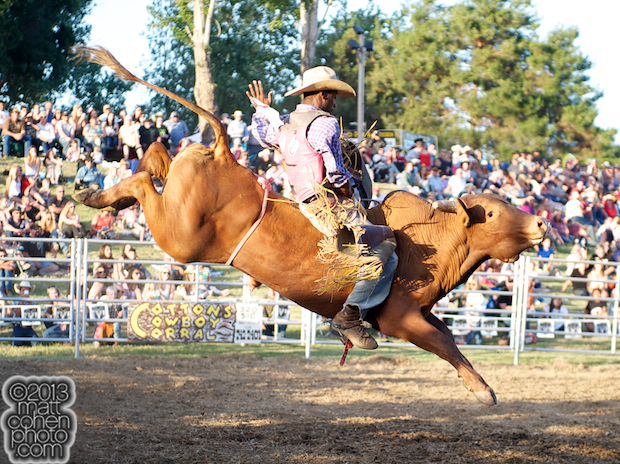Bull rider Chris Byrd of Compton, CA rides an extra at the Marysville Stampede in Marysville, CA.