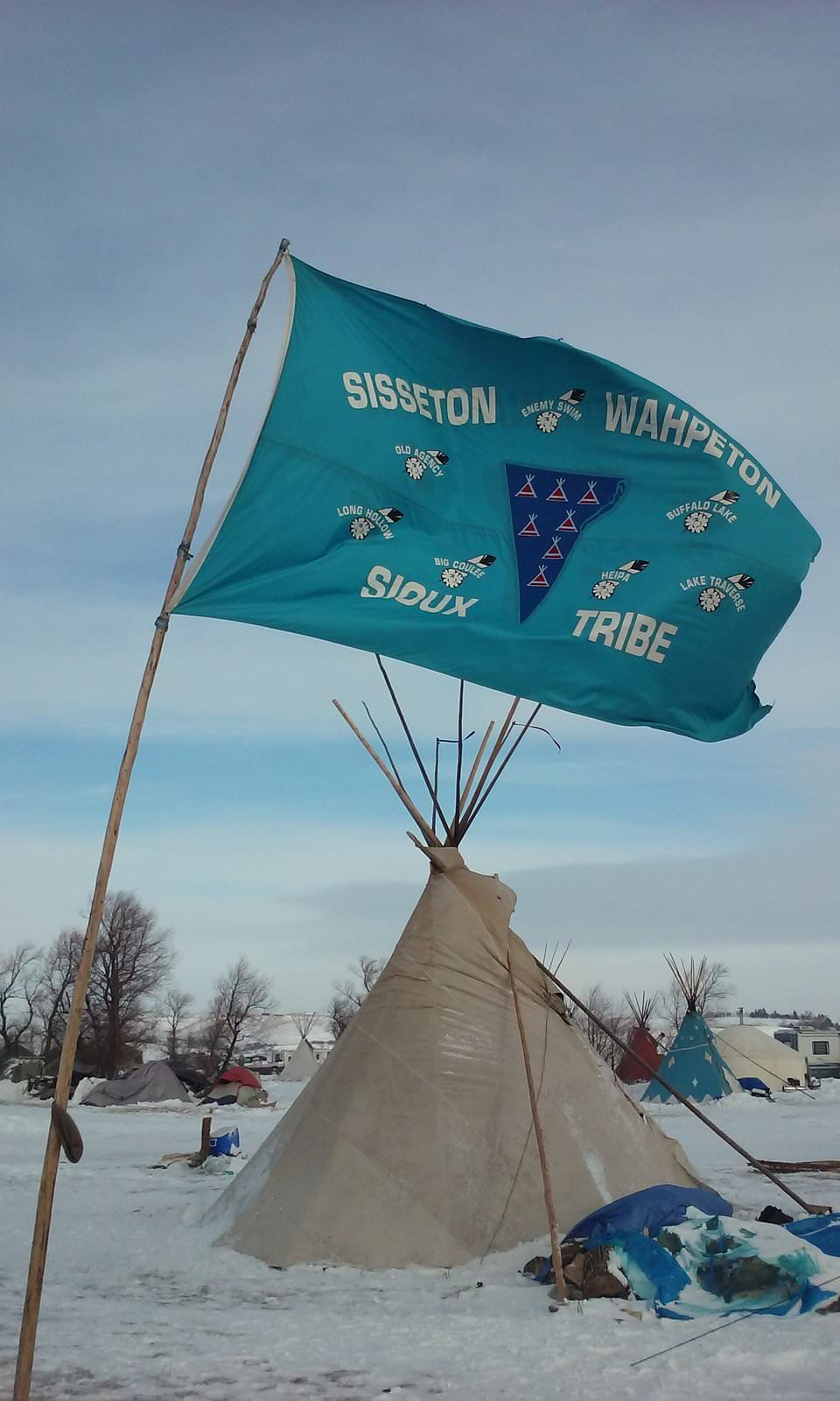 Flag and teepees at Standing Rock. Photo by  Kim Chee.