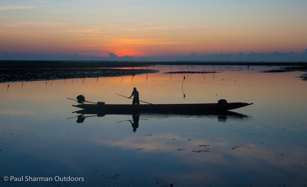 The first light of dawn warms the horizon as a local boatman prepares for the day ahead at Thale Noi in Phatthalung province.