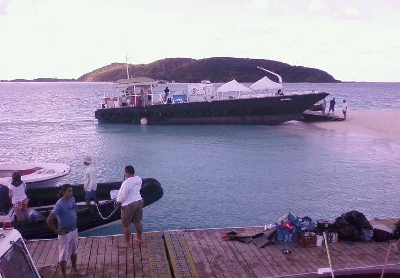 Desembarcando mercancía en una playa con una lancha con la bandera de Estados Unidos (una de varias de nuestras embarcaciones cliente).