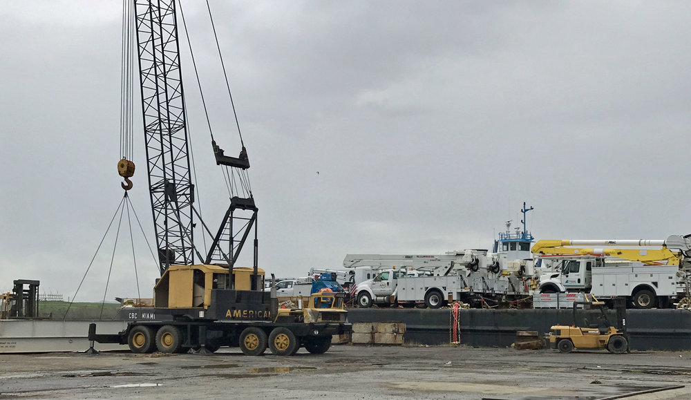 Transcaribbean stevedores using a crane to lift a ramp in place so that the vehicles can be rolled off. Note the Concrete blocks that they found so that the height of the ramp (once in place) will match the deck level of the barge.