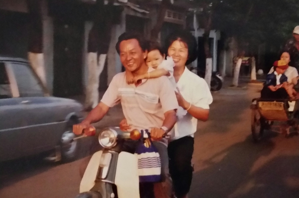 My parents and me on the road, riding extremely safely on our family scooter.
