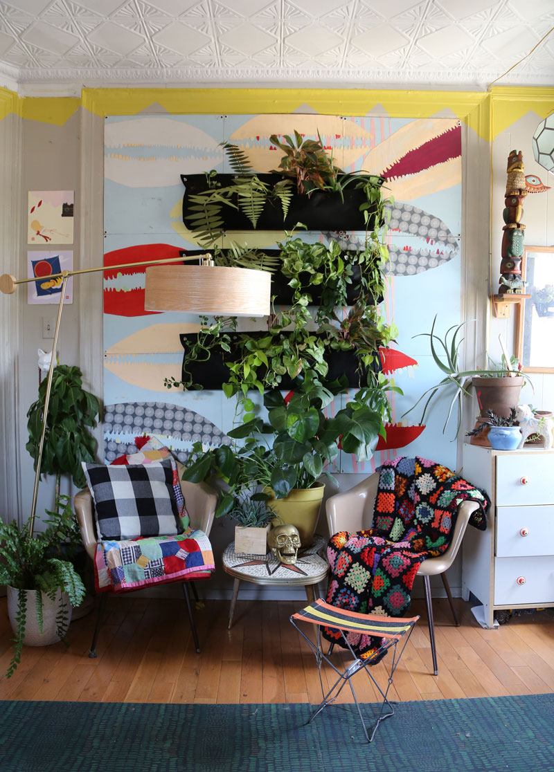 Plants are a huge part of the girls' space. This wall installation of textile collage and living plants makes an incredible focal point in the space. Herman Miller chairs provide a neutral base for an afghan and a crazy quilt, both vintage and colorful. A large statement lamp brings a modern touch to the wall.