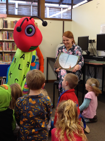 cHILDREN Doug reading at Story Time, with helper Kieren small.png