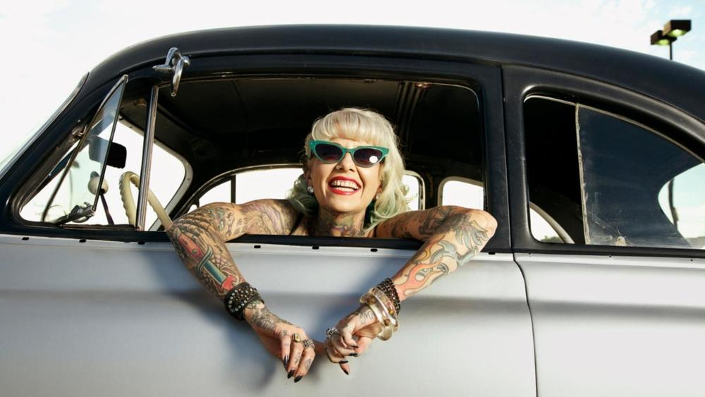 woman with tattoo in a vintage car