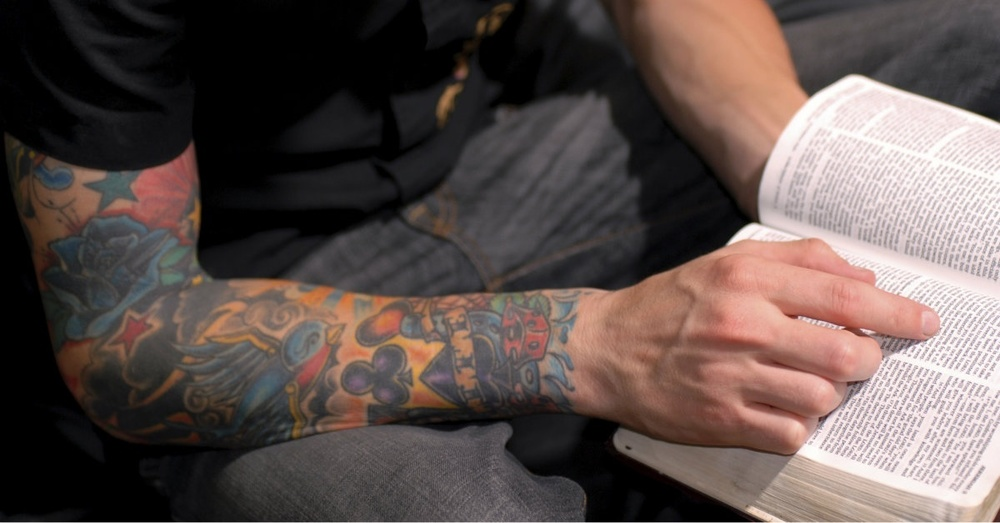 man with tattoos reading