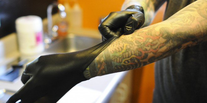 tattoo artist hand with gloves