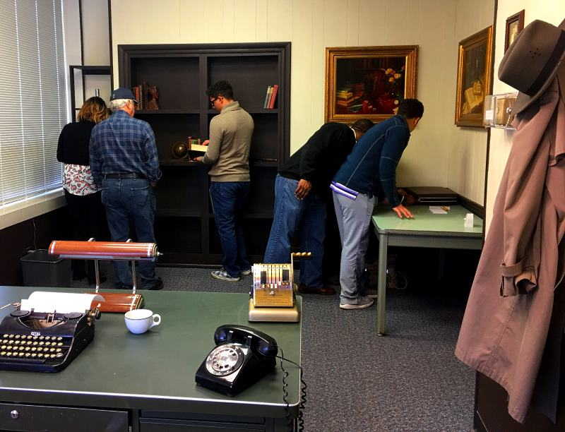 Players search the room for clues left behind by Charlie Swope inside  The Missing Detective's Office ...