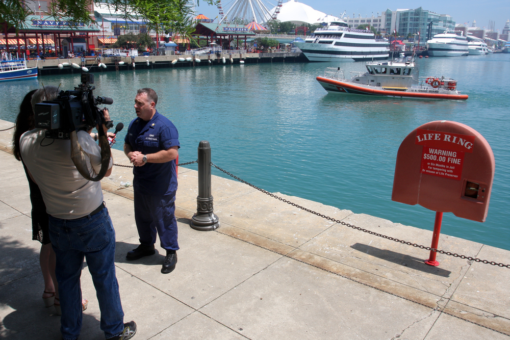 A reporter interviews Petty Officer 1st Class James Strempel about Operation Dry Water at Navy Pier, June 27, 2013. Operation Dry Water is a national boating under the influence awareness and enforcement campaign that lasted June 28-30, 2013. U.S. Coast Guard photo by auxiliarist Jonathan Roth.