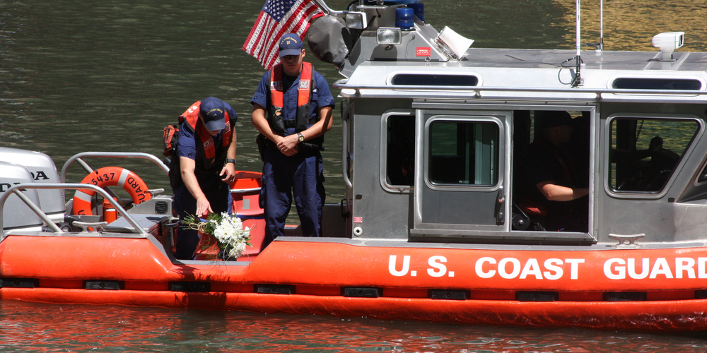 Petty Officer 3rd Class Brennen Coles (left) and Seaman Nicholas Konopka place a bouquet of flowers in the Chicago River in remembrance of the 98th anniversary of the SS Eastland disaster, July 24, 2013. The SS Eastland capsized on the Chicago River in 1915 with more than 2,500 passengers on board. 844 people perished in one of the United States' worst maritime disasters. U.S. Coast Guard photo by auxiliarist Jonathan Roth.