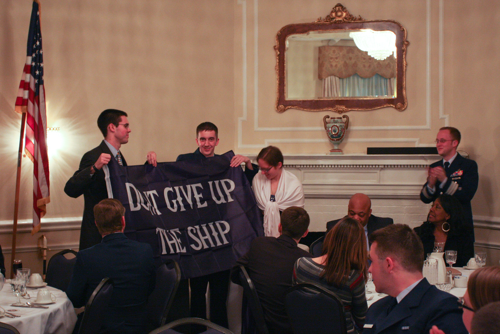"Student leaders from AUP Units Washington, D.C., William & Mary, and Piedmont unfurl a ""Don't Give Up The Ship"" flag from Mr. Welch at AUP Dining Out, March 23, 2013. The gift is meant to guide the students in managing their respective units. U.S. Coast Guard photo by Auxiliarist Jonathan Roth."