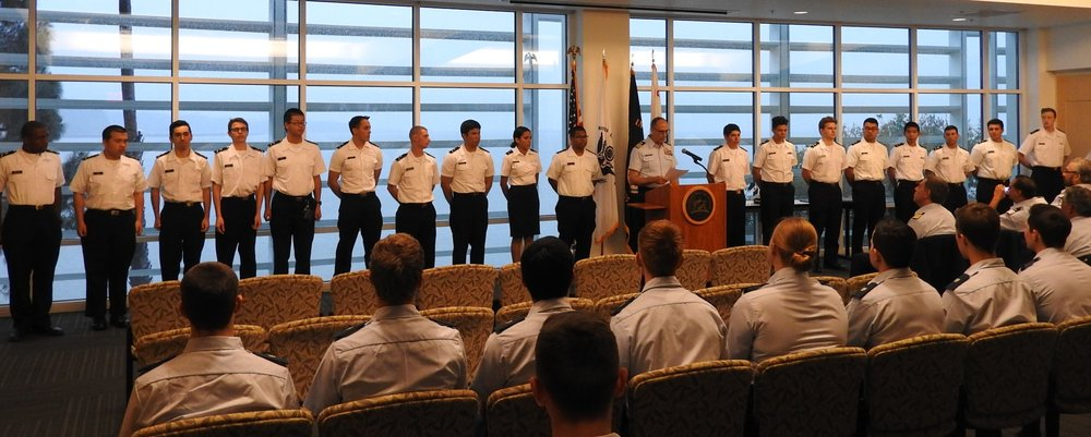 Commander (Ret.) Michael Kazek administering the auxiliary oath before pinning the new AUP seniors. (From right to left: Gary Barker, Dorian Bohorquez, Noah Carter, Oliver Chen, Ezrah Dang, Travis Foster, Amelia Herrman, Charles McDonald, Commander (Ret.) Michael Kazek, Sam Phakhdi, Yaricsa Picon-Carrillo, Kenn Reamico, Sean Resavy, Kolby Saucedo, Briston Siow, Jack Tomasi, Michael Vega, Mijia Wen, Issac Wilkins)