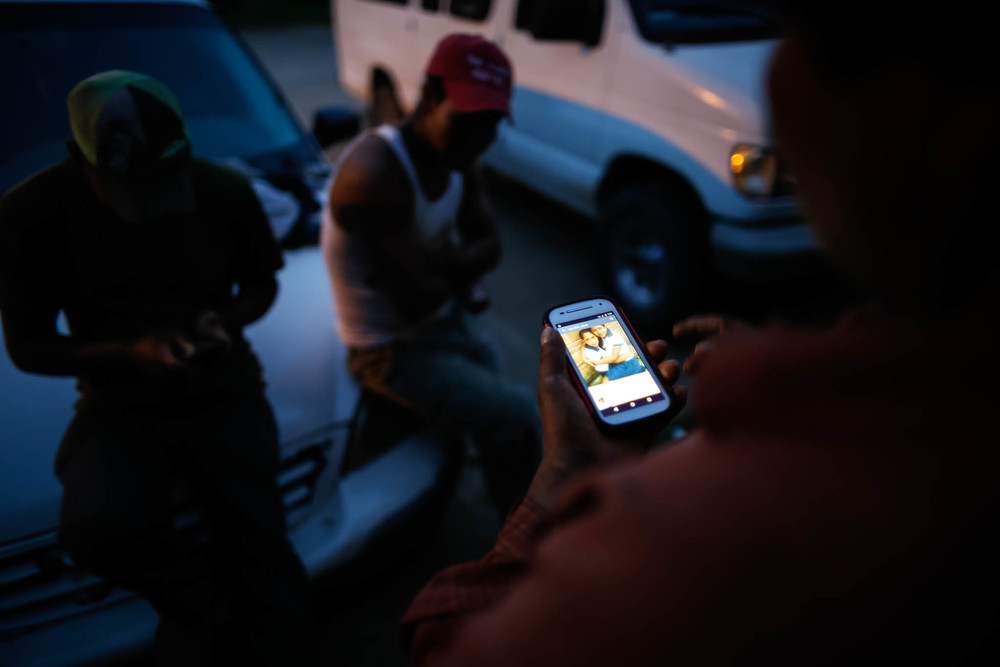 Benjamin Cruz Perez, 42, views a photo of his family in Mexico in front of the apartment he shares with fellow migrant workers.